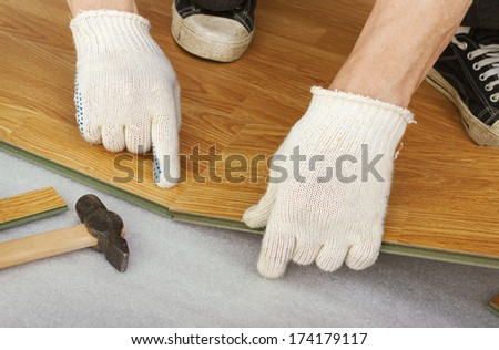 Hands of a master, lay laminate flooring, stylized wood - stock photo