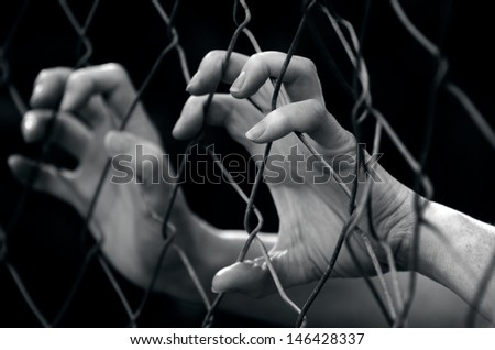Hands of a missing kidnapped, abused, hostage, victim woman in emotional stress and pain, afraid, restricted, trapped, call for help, struggle, terrified, locked in a cage cell. - stock photo