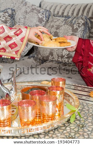Hands of a moroccan woman presenting ramadan cookies and tea to a guest - stock photo