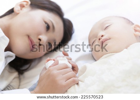 Hands of a Mother holding her baby - stock photo