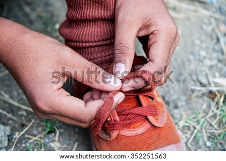 Hands of a needy child tie his shoes. - stock photo
