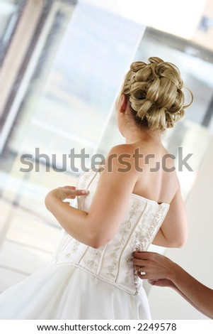 Hands of a person dressing a bride on her wedding day. - stock photo