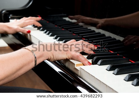 hands of a pianist playing on the keyboard of a grand piano - stock photo