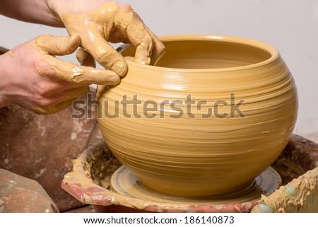 hands of a potter, creating an earthen jar - stock photo