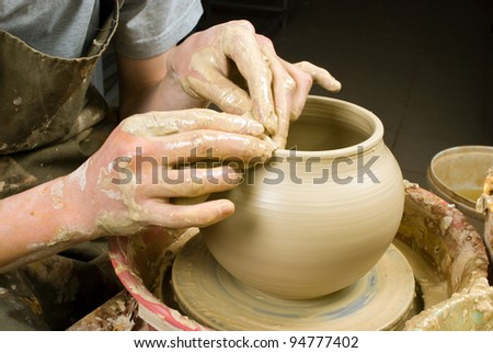 hands of a potter, creating an earthen jar of white clay - stock photo