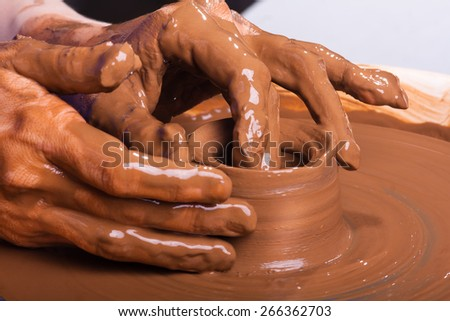Hands of a potter, creating an earthen jar on pottery wheel - stock photo