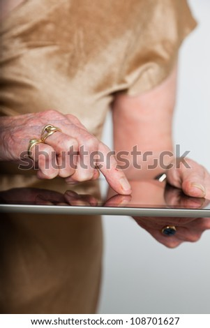 Hands of a senior woman using a tablet. Studio shot on grey background. - stock photo
