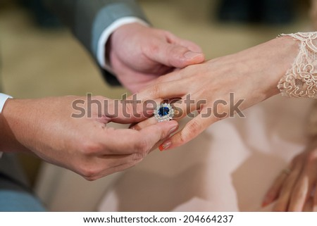 hands of a wedding heterosexual couple. Groom put a ring on finger of his lovely wife. - stock photo