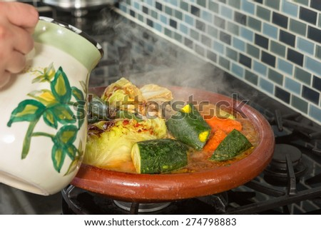 Hands of a woman adding water to a traditional Moroccan tajine during Ramadan nights (Moroccan immigrant woman in modern European kitchen) - stock photo