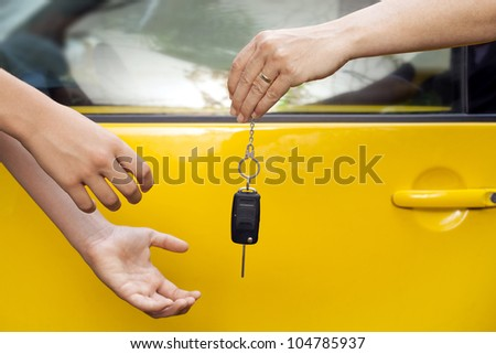 hands of a woman giving car keys to a young boy, outdoor photo - stock photo