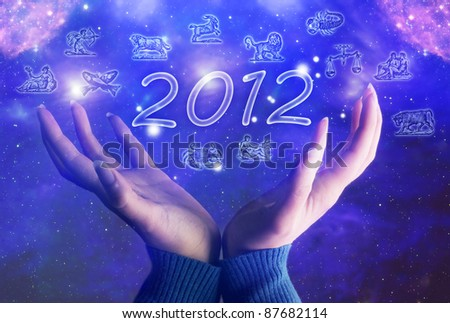 hands of  a woman over background with Universe, 2012 and zodiac symbols - stock photo