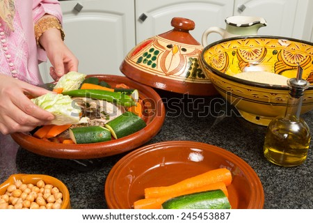 Hands of a woman preparing couscous and a traditional Moroccan tajine during Ramadan nights (Moroccan immigrant woman in modern European kitchen) - stock photo