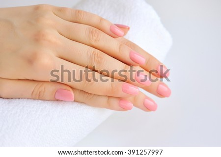 Hands of a woman with pink manicure are on a towel - stock photo