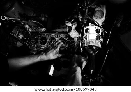 Hands of a worker repairing car motor - stock photo
