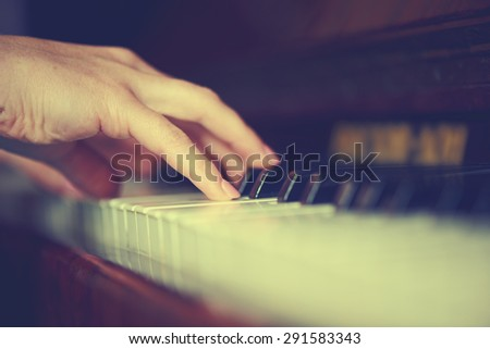 hands of a young woman pianist on the piano keyboard - stock photo