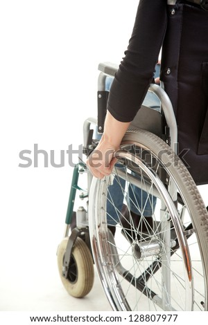 hands of a young woman sitting on a wheelchair, white background - stock photo