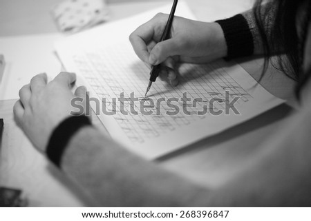 Hands of a young woman taking a calligraphy course - stock photo