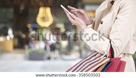 hands of a young woman using mobile phone while walking in shopping district. - stock photo