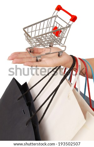 hands of a young woman with lots of shopping bags and cart, isolated on white background - stock photo