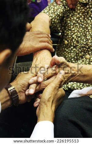 Hands of a Younger holding hands of a senior people - stock photo