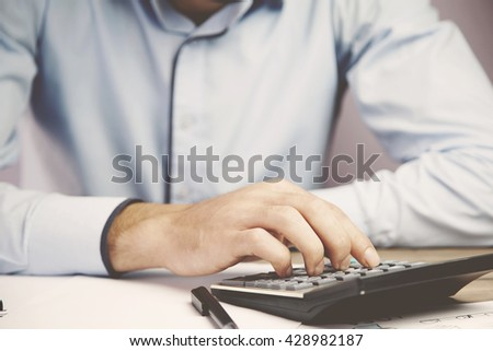 Hands of accountant business man with calculator - stock photo