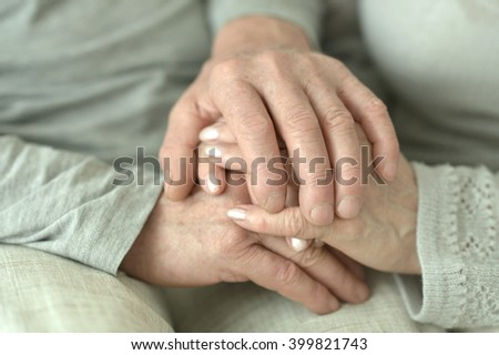 Hands of affectionate elderly couple - stock photo