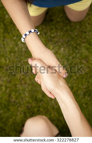 Hands of an adult and a child making a symbolic sign of being friends on green grass background in summertime. Handshake - stock photo
