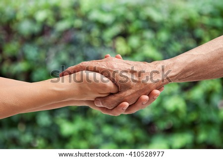 Hands of an elderly senior holding the hand of a woman - stock photo