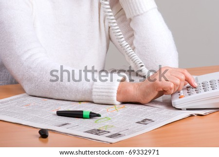 hands of an elderly woman calling on the phone by newspaper ad - stock photo