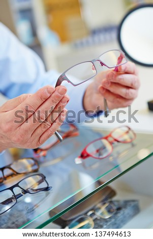 hands of an optician offering new glasses in his retail store - stock photo