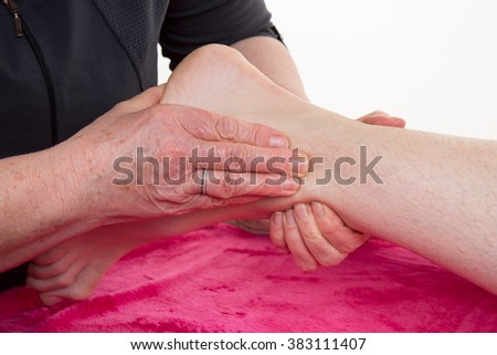 Hands of an osteopath massaging a foot in a room - stock photo