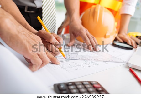 Hands of architects working on blueprints in the office, selective focus - stock photo