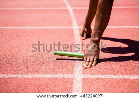 Hands of athlete holding baton on running track - stock photo