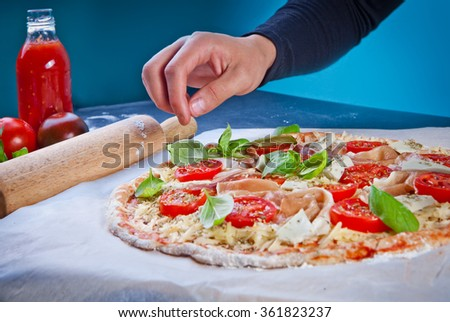 Hands of baker adding ingredients into pizza during pizza preparation at kitchen - stock photo