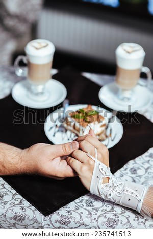 Hands of bride and groom. Cappuccino or latte coffee with heart shape. bride and groom drink a cup of Coffee latte on the date. Happy bride and groom drink a cup of Coffee latte with heart design  - stock photo