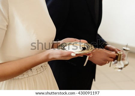 hands of bride and groom preparing for communion at wedding ceremony in church - stock photo