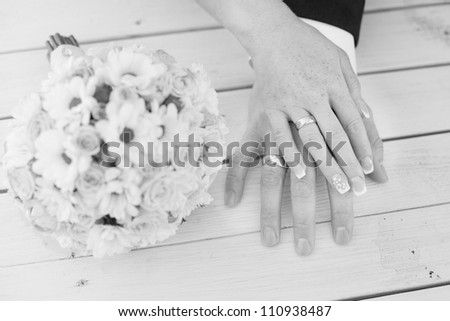 Hands of bride and groom with bouquet black-and-white - stock photo