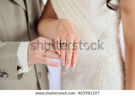 hands of bride and groom with gold rings on wedding - stock photo