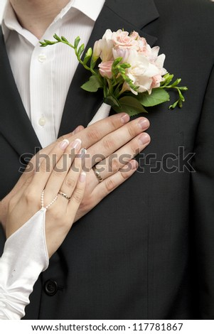 Hands of bride and groom with rings and wedding bouquet - stock photo