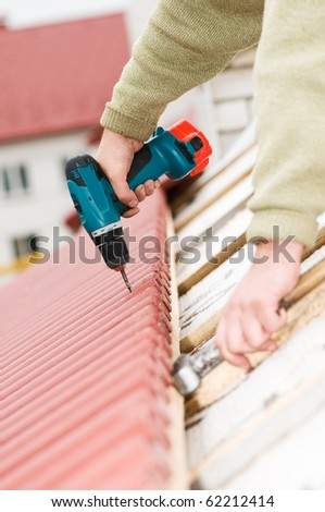 Hands of builder worker at roofing works on tiling with screwdriver - stock photo