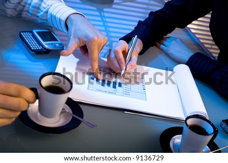 Hands of business people pointing at graph on table. Night time, indoor. - stock photo