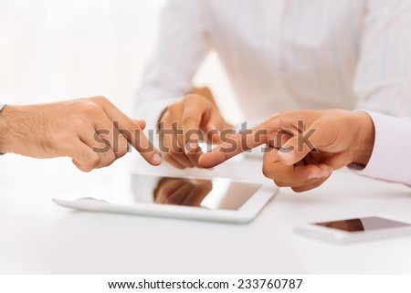 Hands of business people pointing at the digital tablet during the meeting - stock photo