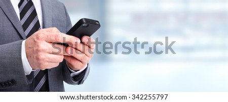 Hands of businessman calling by phone over blue background. - stock photo