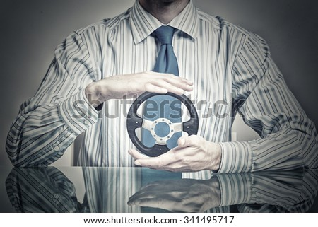 Hands of businessman holding with care car steering wheel - stock photo