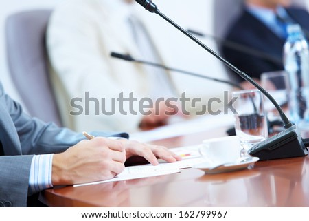 Hands of businessman writing with pen at conference against defocused background - stock photo