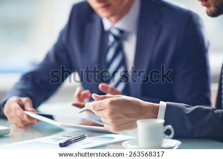 Hands of businessmen working with touchpad - stock photo
