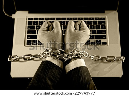 Hands of caucasian businessman addicted to work tied and bond with iron chain handcuffed to computer laptop in workaholic, internet slave and addict concept in black and white - stock photo