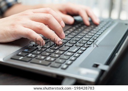 Hands of caucasian man on keyboard of laptop - stock photo
