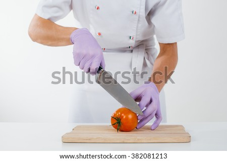 Hands of chef in gloves slicing tomato - stock photo