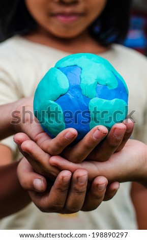 Hands of child holding colorful clay model of Planet Earth - stock photo